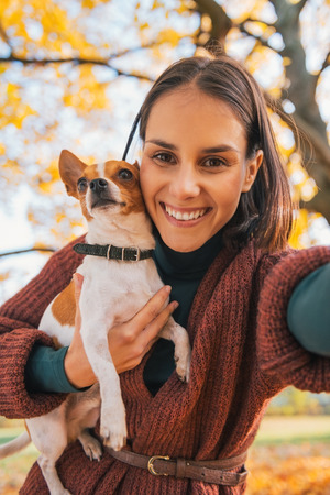 dog park: Portrait of smiling young woman with dog outdoors in autumn making selfie