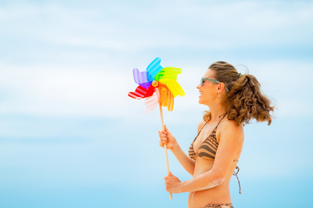 Happy young woman playing with colorful windmill toy on beach