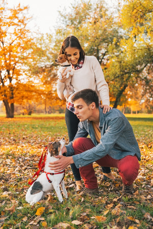 perros jugando: Feliz pareja joven con perros que juegan al aire libre en el Parque de oto�o Foto de archivo