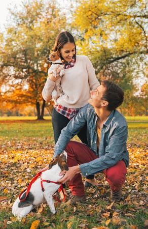dogs playing: Feliz pareja joven con perros que juegan al aire libre en el Parque de oto�o Foto de archivo