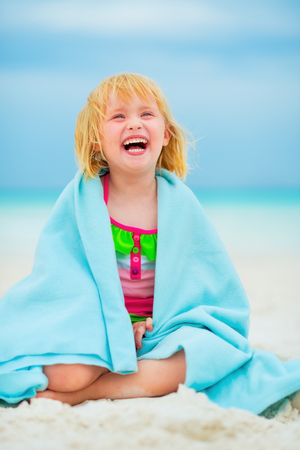 beach wrap: Portrait of laughing baby girl wrapped in towel sitting on beach Stock Photo