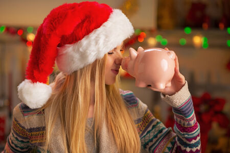 thrift box: Portrait of smiling teenager girl in santa hat with piggy bank