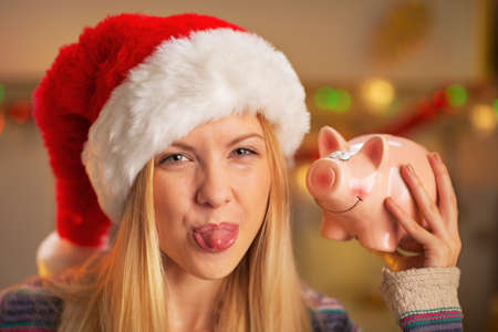 thrift box: Portrait of teenager girl in santa hat showing tongue and piggy bank