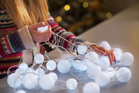 untangle: Closeup on happy teenager girl in santa hat untangling christmas lights