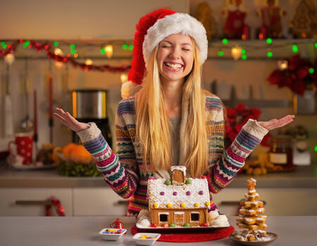 Portrait of happy teenager girl in santa hat with christmas cookie house in christmas decorated kitchen