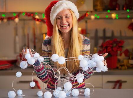 untangle: Portrait of happy teenager girl in santa hat untangling christmas lights Stock Photo