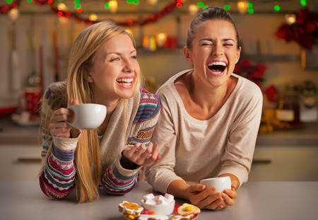 Portrait of laughing girlfriends having christmas snacks in christmas decorated kitchen Foto de archivo