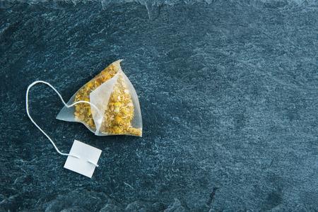 substrate: Closeup on camomile tea bag on stone substrate