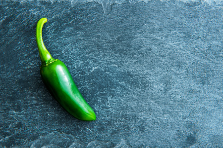 substrate: Closeup on green chili pepper on stone substrate