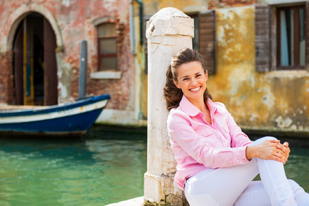 Portrait of smiling young woman sitting on street in venice, italy photo