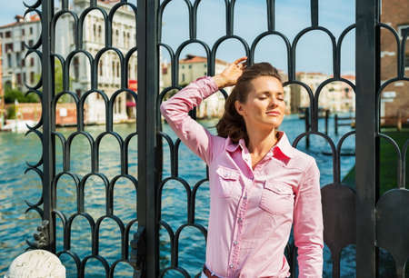 Portrait of relaxed young woman on grand canal in venice, italy photo