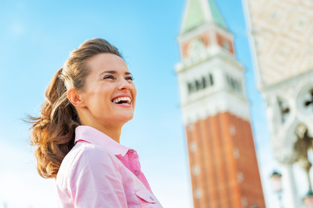 Portrait of happy young woman against campanile di san marco in venice, italy photo