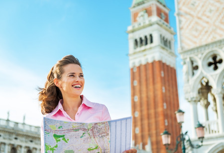 the campanile: Portrait of smiling young woman looking at map against campanile di san marco in venice, italy