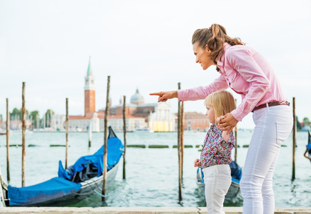 Mother pointing baby on something on grand canal embankment in venice, italy photo