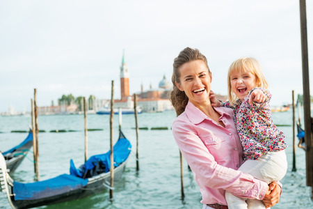 Portrait of happy mother and baby on grand canal embankment in venice, italy Reklamní fotografie