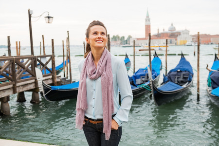 Happy young woman standing on embankment in venice, italy photo