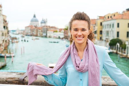 Portrait of happy young woman standing on bridge with grand canal view in venice, italy