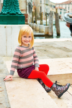 Baby girl sitting on embankment in venice, italy photo