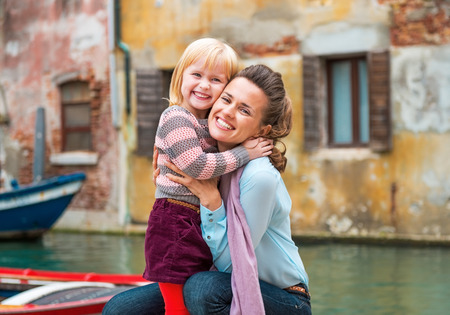 on vacation: Portrait of happy mother and baby girl hugging while in venice, italy