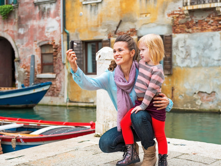 Happy mother and baby girl making selfie in venice, italy photo