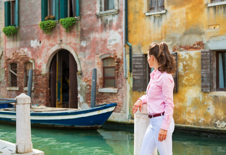 Young woman looking on canal in venice, italy. rear view photo