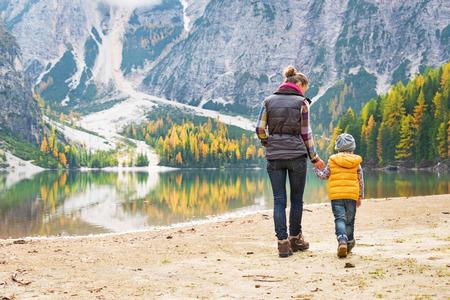 Moeder en baby lopen op meer Braies in Zuid-Tirol, Italië. achteraanzicht