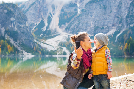 Gelukkige moeder en baby maken selfie op meer Braies in Zuid-Tirol, Italië