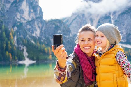 Madre y el bebé feliz que hace Autofoto en braies lago en Tirol del Sur, Italia