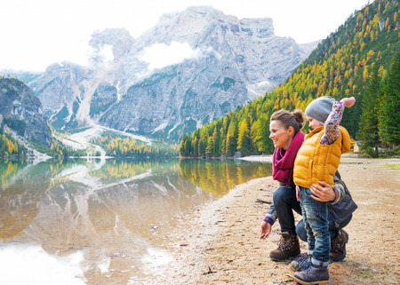 traveller: Mother and baby throwing stones on lake braies in south tyrol, italy