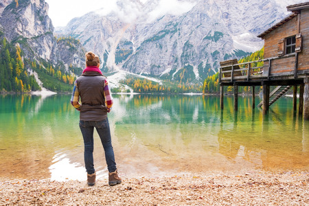anonym: Full length portrait of young woman on lake braies in south tyrol, italy. rear view Stock Photo