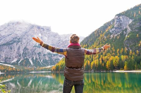 Young woman on lake braies in south tyrol, italy rejoicing. rear view