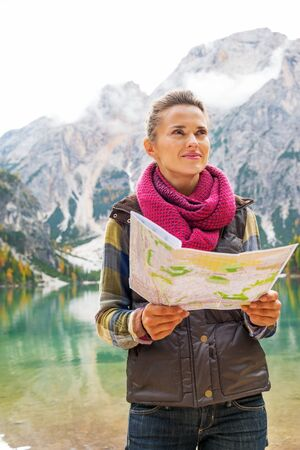 Young woman with map on lake braies in south tyrol, italy photo