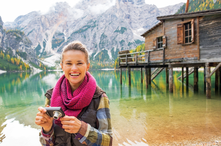 Portrait of young woman with photo camera on lake braies in south tyrol, italy Stock Photo - 99980412
