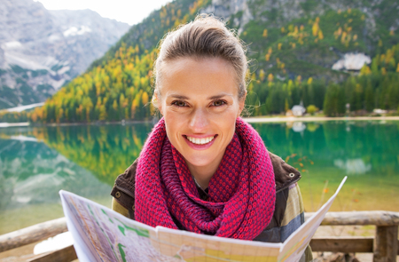 Portrait of happy young woman with map on lake braies in south tyrol, italy photo