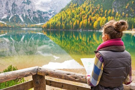 Young woman with map on lake braies in south tyrol, italy. rear view photo