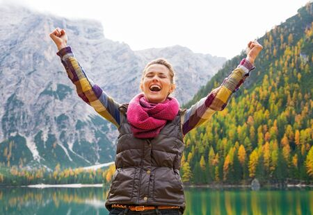 Happy young woman on lake braies in south tyrol, italy rejoicing