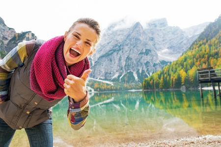 thumbs up gesture: Happy young woman on lake braies in south tyrol, italy showing thumbs up