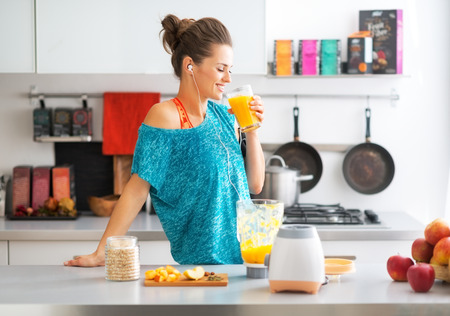 Happy fitness young woman drinking pumpkin smoothie in kitchen Imagens