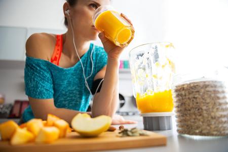 Primer plano de la aptitud joven mujer bebiendo batido de calabaza en la cocina Foto de archivo
