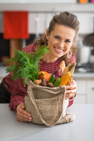 Portrait of smiling young housewife with vegetables from local market photo