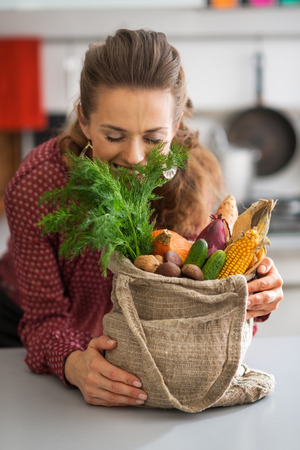 Happy young housewife enjoying freshness of vegetables from local market
