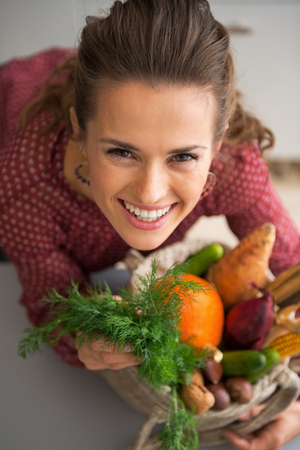 Portrait of happy young housewife with shopping bag of fresh vegetables from local market photo
