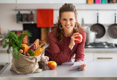 Retrato de joven ama de casa feliz celebración de cheques de compra de comestibles en la cocina