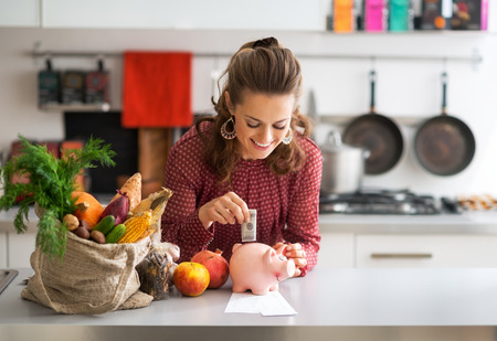 frugality: Portrait of happy young housewife putting money into piggy bank after shopping on local market