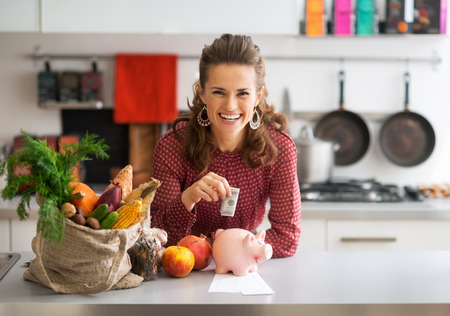 Portrait of happy young housewife putting money into piggy bank after shopping on local market