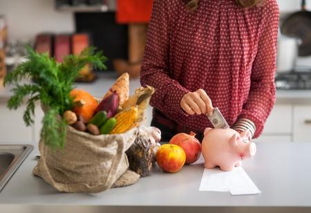 Close-up op jonge huisvrouw geld steken in piggy bank na het winkelen op de lokale markt