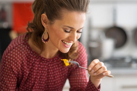 eating: Portrait of happy young woman eating in kitchen Stock Photo