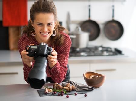 Retrato de feliz fotógrafo alimentación femenina control de las fotos en la cámara