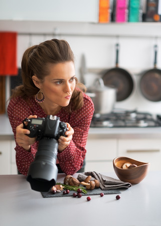disquieted: Concerned female food photographer checking photos in camera Stock Photo