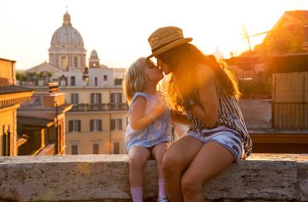 Moeder en baby meisje kussen zittend op straat met uitzicht op de daken van rome op zonsondergang